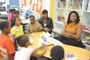 Tanika Island (left, in gray) observes Kandice Washington's second-grade UChicago charter classroom before coaching Washington in the school's instructional system.