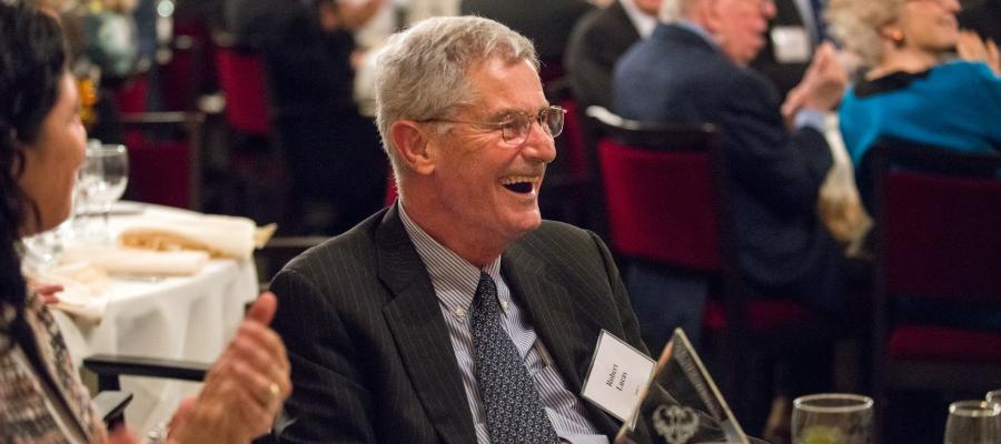 Robert E. Lucas, Jr. listens to his colleagues' remarks during the award dinner.