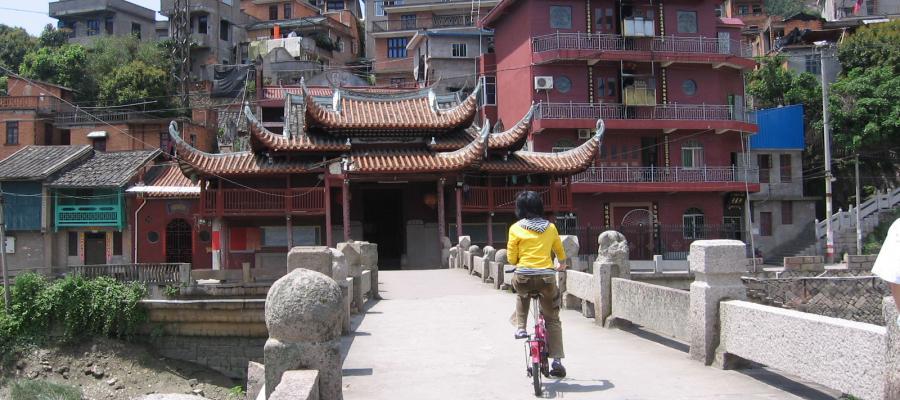 Woman biking through Chinese city