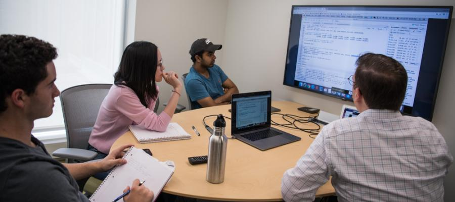 From Professor Gulotty's left, student research team members Stanley Shapiro, Di Yang, and Vivek Saini discuss the project. Minju Kim, a PhD student in Political Science, (not pictured) also joined by conference.